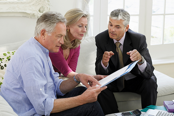 financial advisor counseling a retired couple in their home