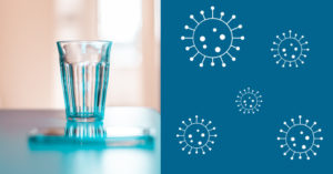 Empty glass sitting on table next to coronavirus icons